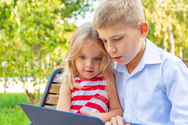 Smiling brother and sister sitting on bench in park and playing on laptop