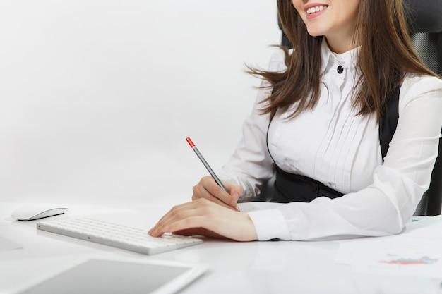 정장을 입고 안경을 쓰고 책상에 앉아 있는 웃고 있는 갈색 머리 비즈니스 여성, 밝은 사무실에 문서가 있는 현대적인 모니터가 있는 컴퓨터에서 일하고 있습니다. 확대