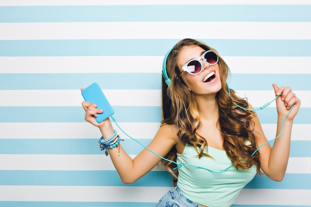 Smiling brown-haired girl enjoying favorite song and dancing in turquoise tank-top. close-up indoor portrait of excited curly young woman having fun in headphones with phone on striped wall.