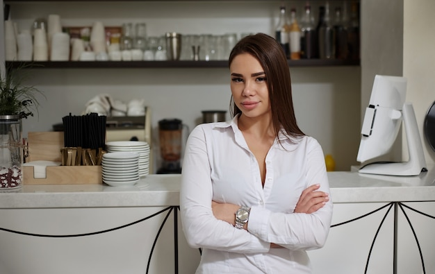 A smiling brunette barista in white shirt stands at the bar
