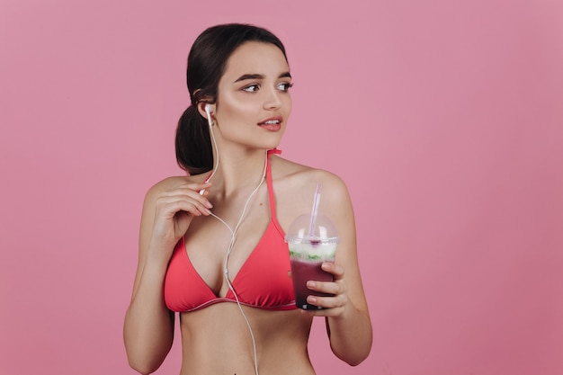 Smiling brunette in a bikini stands with earphones and cold cocktail