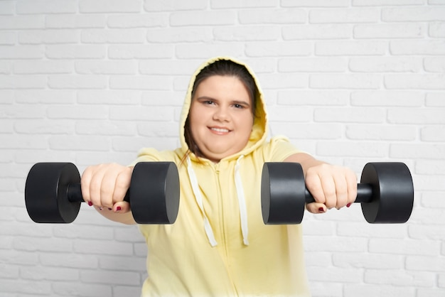 Smiling brunette chunky young lady in yellow hoodie looking at camera and holding two big black dumbbell on her hands with white wall behind.fat woman is seriously set to bring herself into good shape