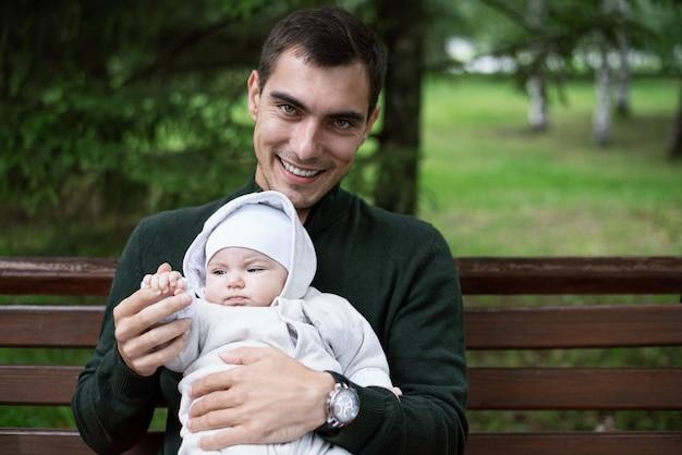Улыбающийся папа-брюнетка в куртке reen сидит на скамейке с ребенком на руках в парке, концепция счастливого отцовства