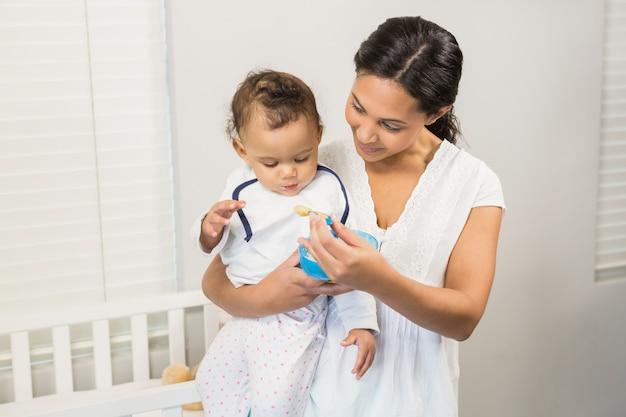 Smiling brunette feeding baby in bedroom