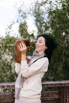 그녀의 팔에 작은 갈색 개를 들고 웃는 갈색 머리 소녀