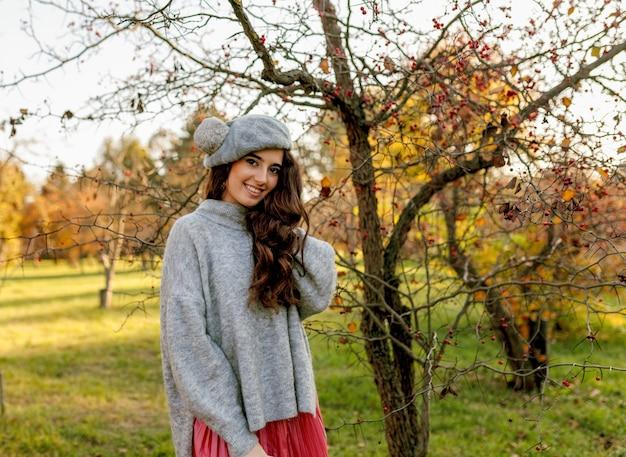 Улыбающаяся брюнетка в осеннем наряде и берете стоит среди желтых деревьев в парке. осень на открытом воздухе.