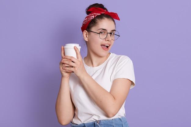 Улыбающаяся брюнетка в белой повседневной футболке держит чашку кофе, изолированную над сиреневым пространством, смотрит в камеру, держит рот открытым