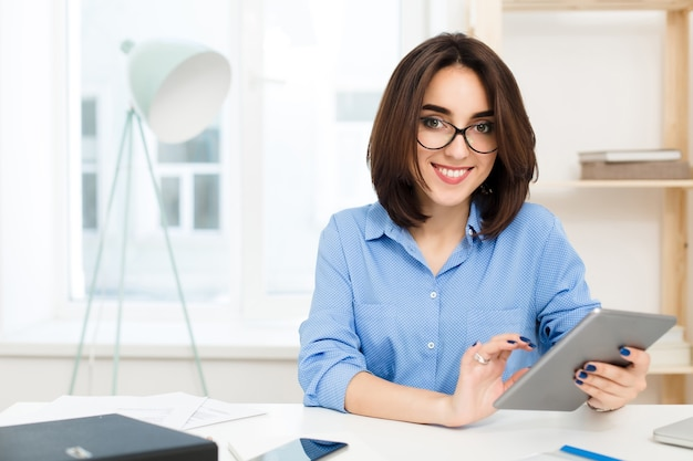 A smiling brunette girl is sitting at the table in office. she wears blue shirt and black glasses. she works with tablet.