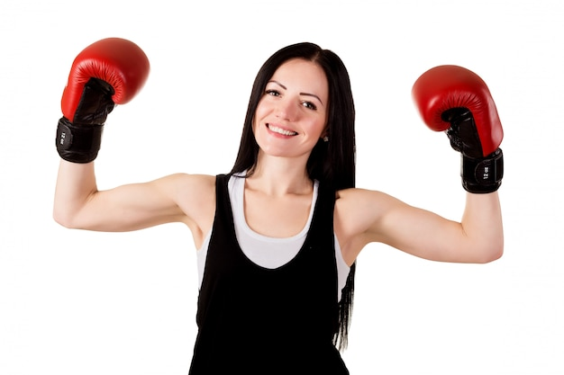 Smiling brunette girl with long hair in red boxing gloves raised their hands up