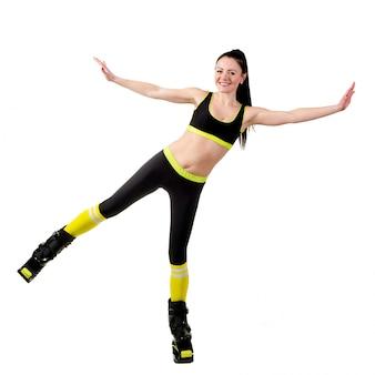 캉 구에서 긴 머리 훈련 웃는 갈색 머리 소녀 신발 점프.