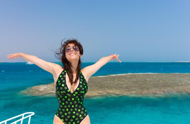 ヨットの上に立って、晴れた夏の日に手を広げて、黒緑色の水着でブルネットを笑顔、そよ風が髪を開発し、背景に美しいターコイズブルーの海