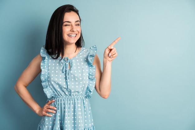水玉模様のドレスでブルネットの笑顔はコピースペースに指を示しています