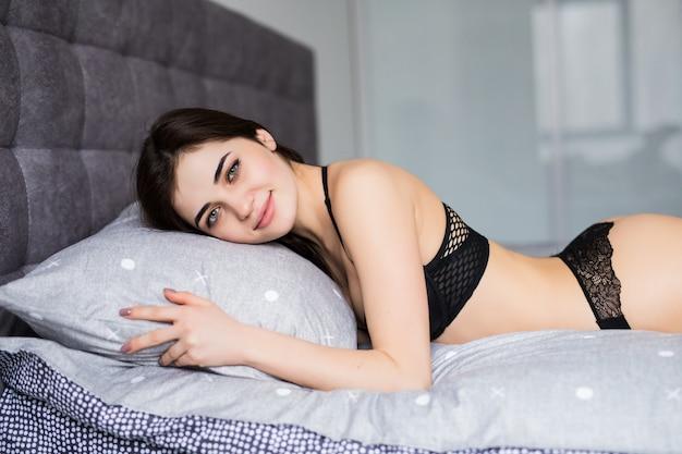 Улыбающаяся брюнетка лежит в своей постели в яркой спальне