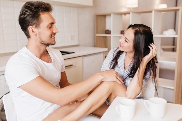 Uomo brunetta sorridente che tocca il ginocchio della fidanzata mentre lei posa allegramente in cucina