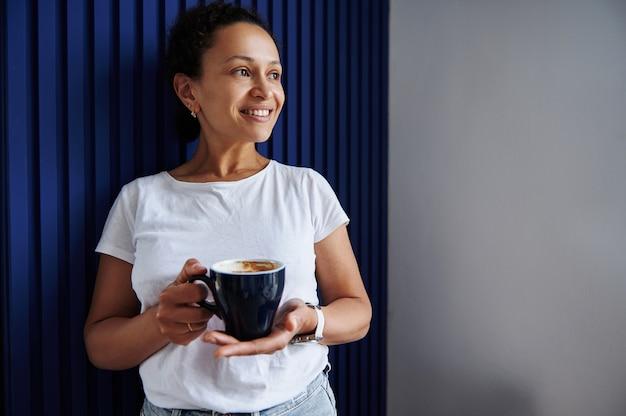 エンボス加工の青い壁に寄りかかって手にコーヒーを飲みながら笑顔のブルネットの成熟した女性。ホットドリンクのカップを持つ美しい女性の肖像画