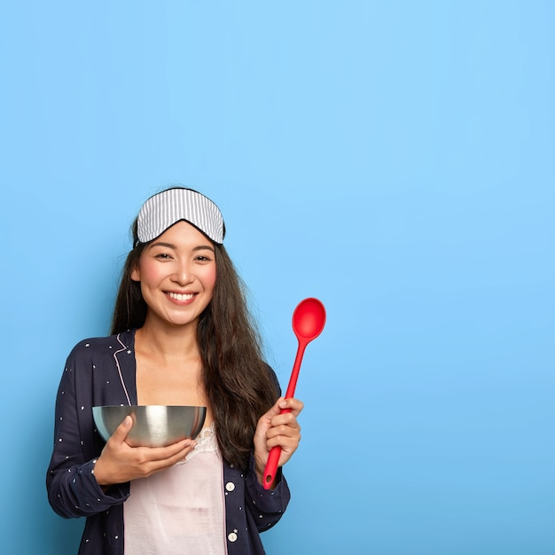 Smiling brunette mixed race woman holds spoon and bowl, glad to try new recipe of delicious dish, wears sleepmask and slumber suit, makes healthy breakfast