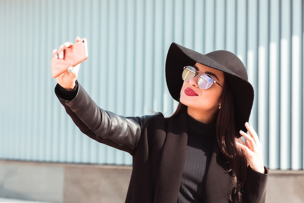 携帯電話で自分撮りをしているブルネットモデルの笑顔。女性は帽子とサングラスを着用します