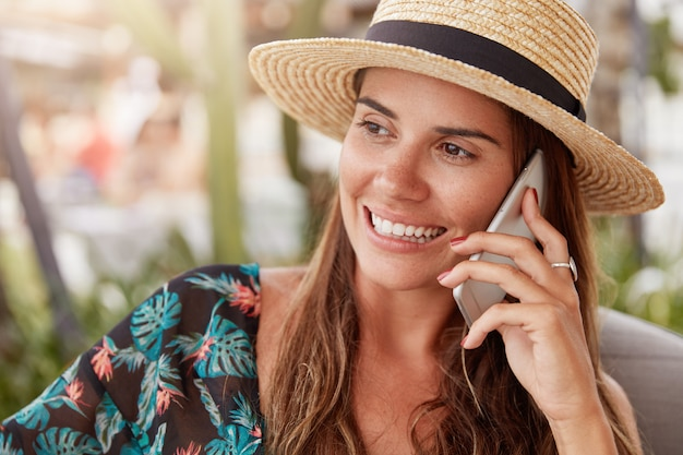 Smiling brunette restful female in straw hat has pleasant conversation with friend, tells about summer holidays in exotic country, uses modern cell phone for keeping in touch. communication and rest