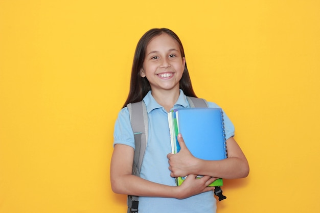Smiling brunette schoolgirl hugs textbooks notebooks while studying at school on yellow background