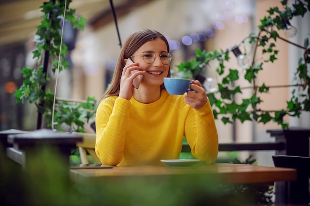 Smiling brunette sitting on terrace of cafe, holding cup of coffee and chatting with friend on a phone.
