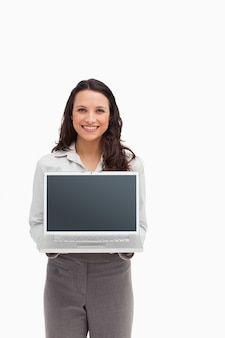 Smiling brunette standing while showing a laptop screen