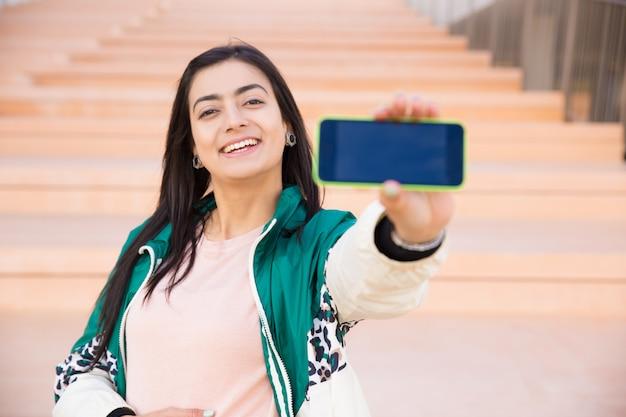 스마트 폰으로 갈색 머리 복용 selfie 미소