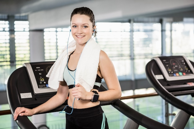 Smiling brunette on treadmill looking at the camera at the gym