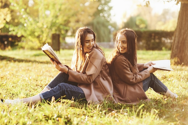 Smiling brunette twin girls sitting back to back on the grass and looking at each other, legs slightly bent in knees, with brown books in hands, wearing casual coat in autumn park on blurry background