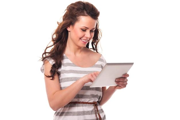 Bruna sorridente utilizzando la tavoletta digitale