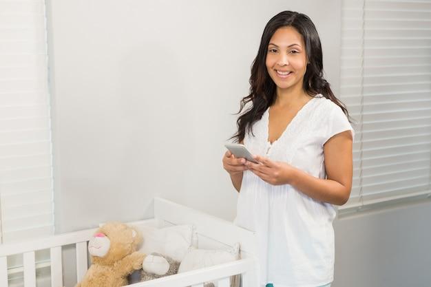 Smiling brunette using smartphone near a crib
