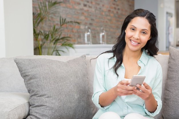 Smiling brunette using smartphone on the sofa