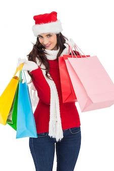 Smiling brunette in winter wear holding shopping bags