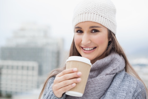 Smiling brunette with winter clothes on holding mug of coffee