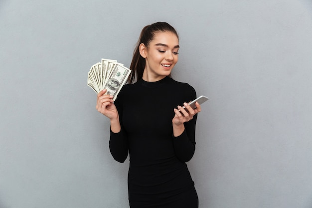 Smiling brunette woman in black clothes holding money