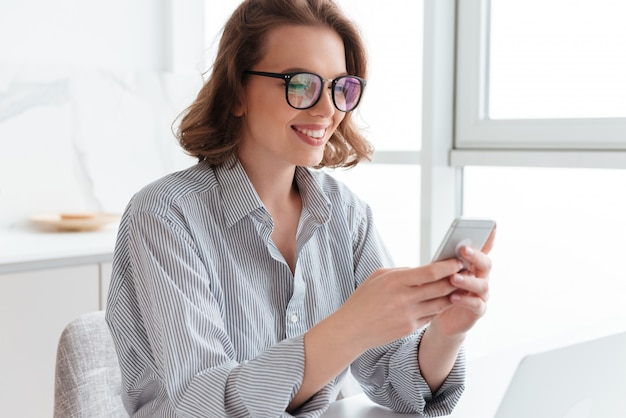 Smiling brunette woman in glasses texting message on smartphone while sitting at kitchen
