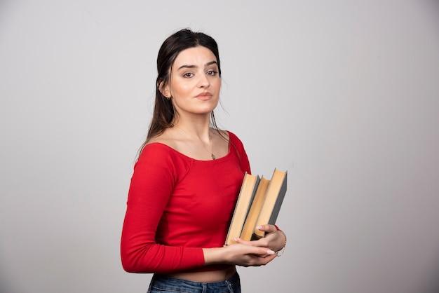 Sorridente donna bruna che tiene i libri in mano.