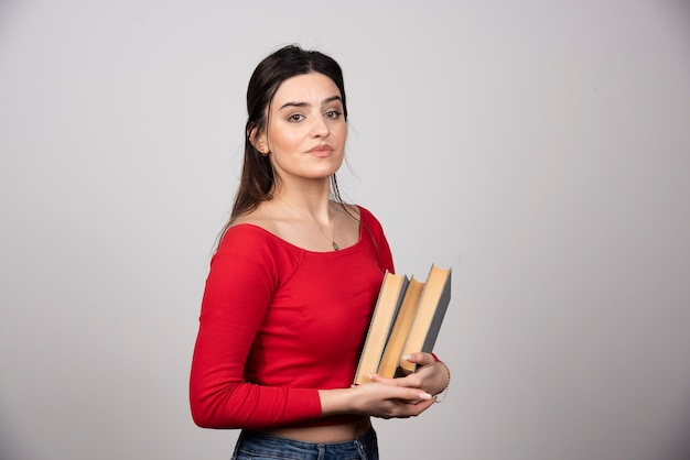 Улыбается брюнетка женщина, держащая книги в руках.