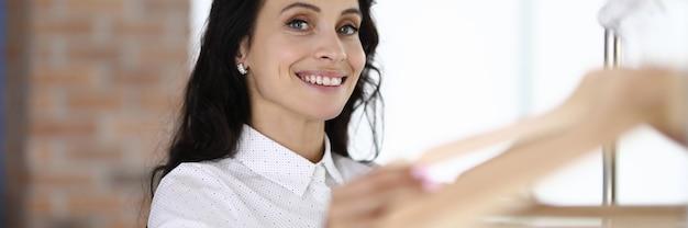 Улыбаясь брюнетка женщина, держащая пустые вешалки за руку. наполнение гардероба и рисование концепции модных луков