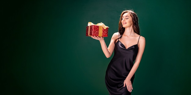 검은 드레스를 입은 웃고 있는 브루네트 여성은 황금 활 휴가 컨셉으로 선물 빨간 상자를 들어 올립니다