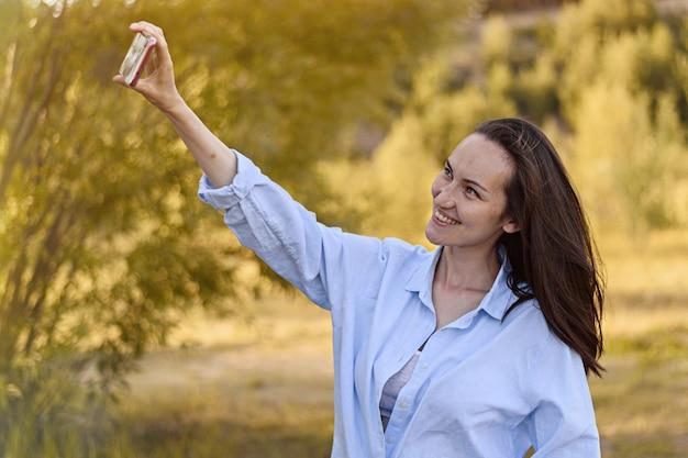 青いシャツの笑顔のブルネットの女性はスマートフォンで自分撮りを取ります