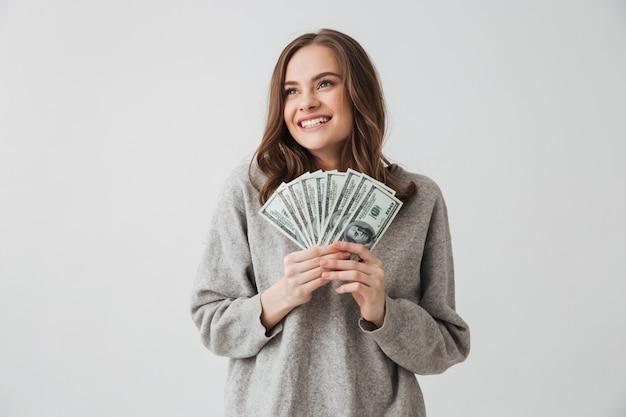 Улыбающаяся брюнетка женщина в свитере держит деньги, глядя на серую стену