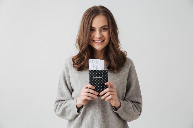 Улыбающаяся брюнетка в свитере готовится к поездке, держа паспорт с билетами над серой стеной