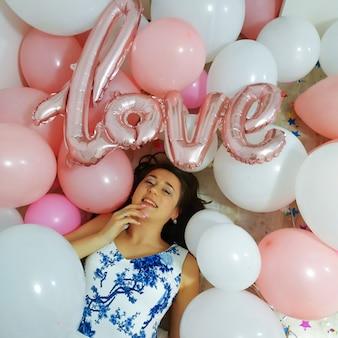 Baloons에 누워 흰색과 파란색 드레스에 웃는 갈색 머리 여자. 파티를 위한 흰색과 분홍색 풍선과 색종이가 있는 생일 장식. 생일 기념일을 축하합니다. 단어 사랑으로 여자 파티