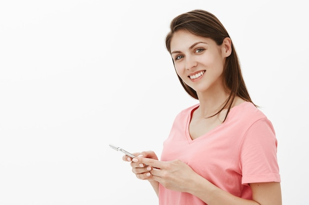 Улыбающаяся брюнетка женщина позирует в студии со своим телефоном