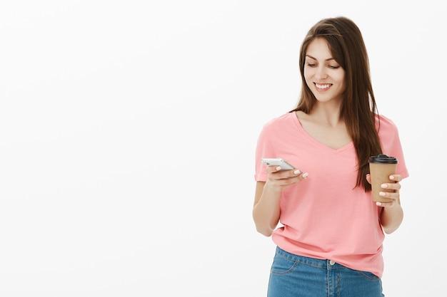 Sorridente donna bruna in posa in studio con il suo telefono e caffè