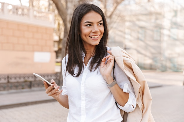 Smiling brunette woman in shirt holding her jacket
