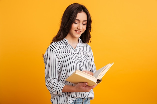 Smiling brunette woman in shirt reading book