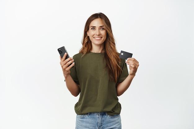 Улыбающаяся брюнетка женщина показывает свою кредитную дисконтную карту, держит мобильный телефон смартфона и выглядит довольным спереди