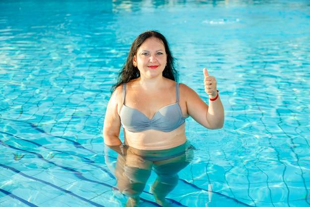 Улыбающаяся брюнетка женщина стоит в бассейне показывает класс.