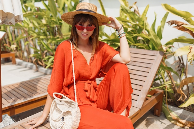 Smiling brunette woman in stylish orange outfit and straw hat chilling on deck chair near pool.